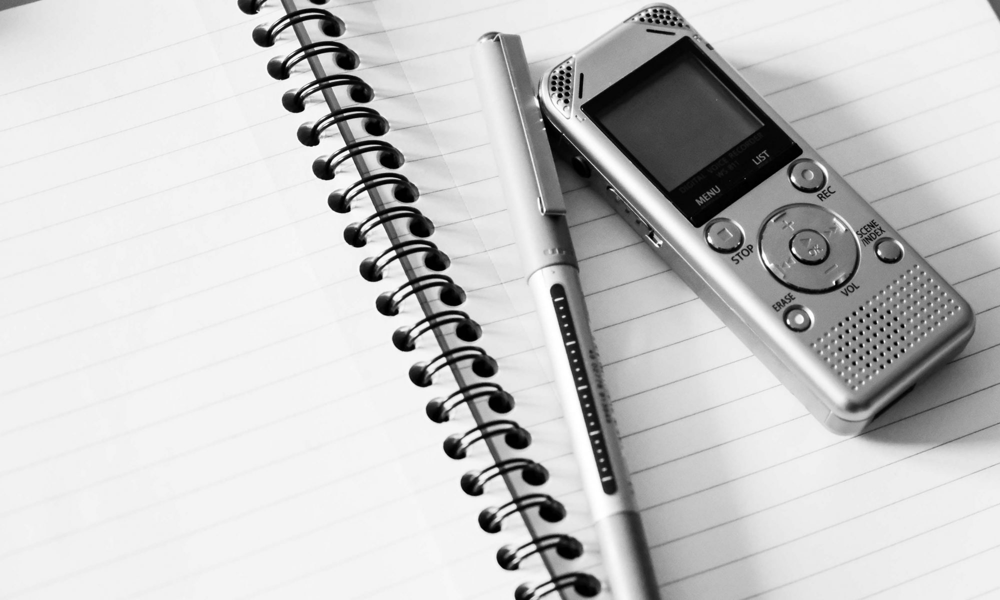 a dictaphone and pen sits on a spiral bound notepad