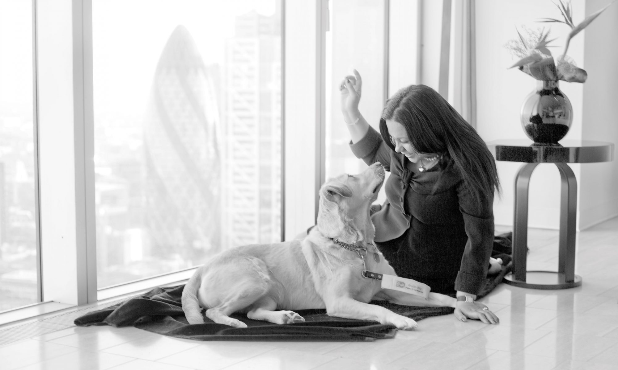 Katia Ramo and her guide dog Cora sit on the floor in front of a wide window with a view over the city of london